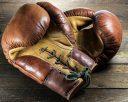 alte Boxhandschuhe auf rustikalem Holzhintergrund